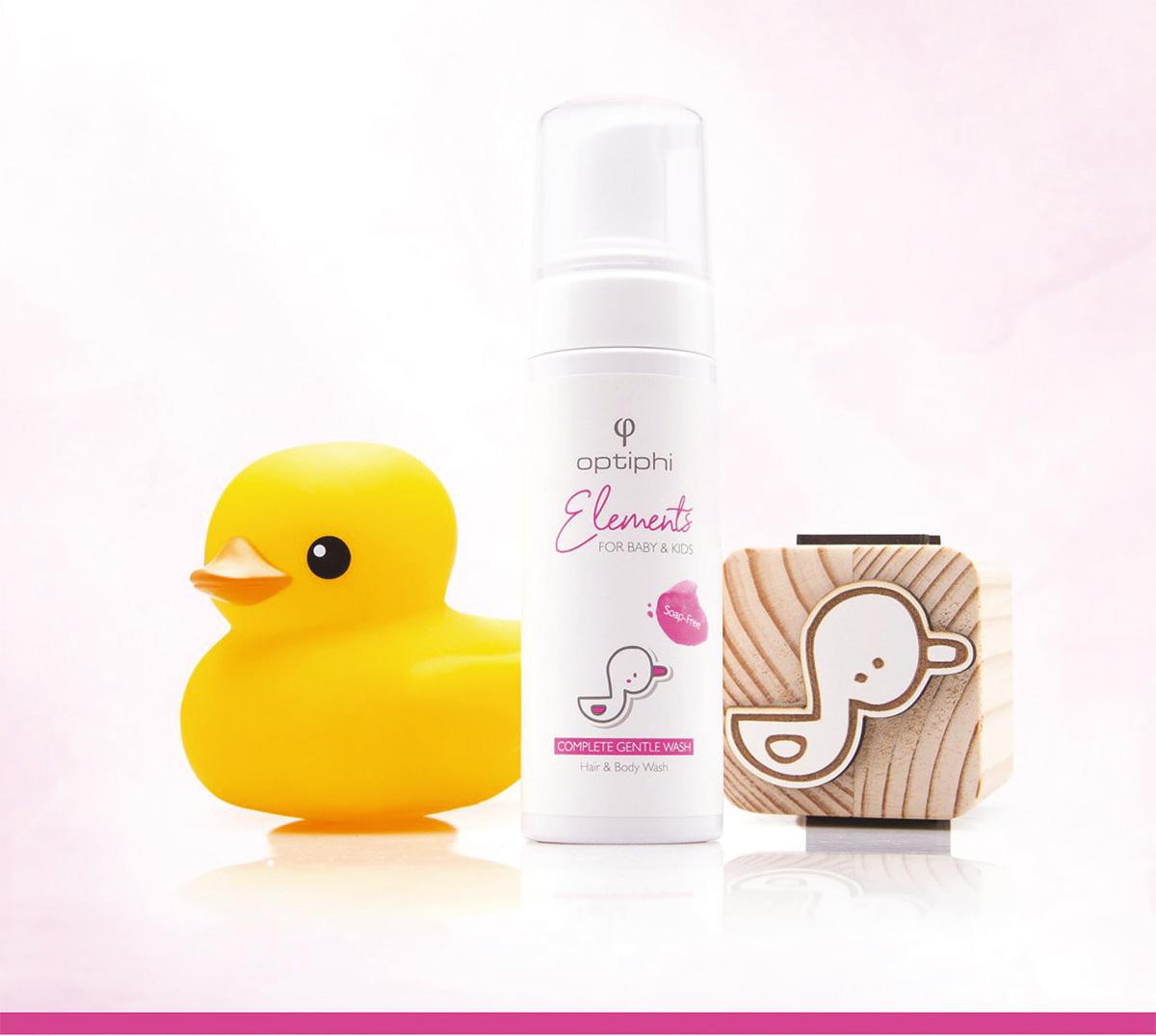 Die seifenfreie Haar- & Körperwäsche Produktfoto: Weiße Pumpflasche mit Aufschrift in Pink. Baby Haar und Bodywaschgel. Rechts ein Holzwürfel der eine Zeichnung mit einer Ente zeigt. Links eine gelbe Badeente