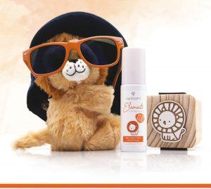 Der mineralische Sonnenschutz Kleiner Plüschlöwe mit rotbrauner viel zu großer Sonnenbrille und zu großen schwarzen Hut mit Baby Sonnenpflege Produkt und Holzwürfel mit handgemalten Löwen