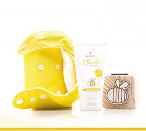 Die optimale Pflege für Baby´s Po Produktfoto: Gelbe kleine Produkttasche. In der Mitte eine weiße Tube mit gelber Aufschrift Baby Bum, links Holzwürfel mit Skizze einer Biene.