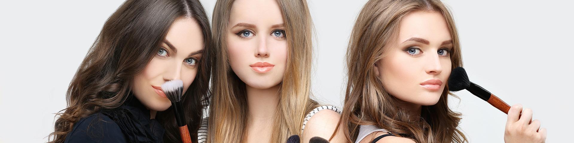 3 junge Frauen links mit schwarzen langen Haar, in der Mitte blond und recht mit braunen langen Haar. Die Damen halten Kosmetikpinsel zum Gesicht