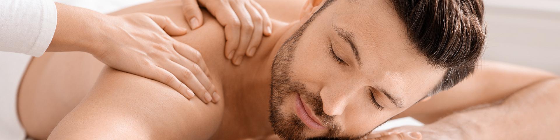 Massage -Junger Mann mit Bart liegt entspannt am Bauch. Er wird an der Schulter massiert