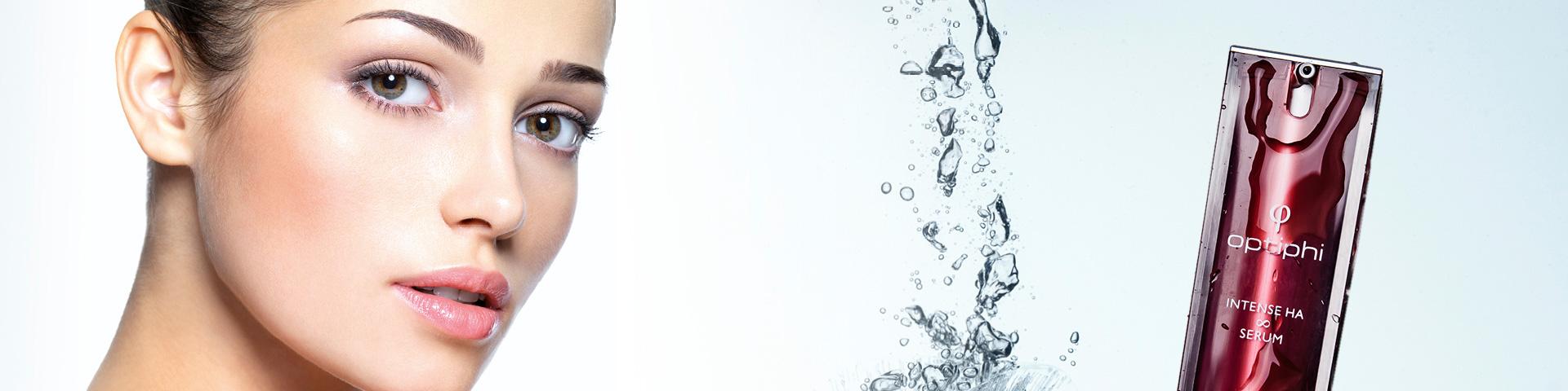 Kosmetikbehandlung Junges Frauengesicht mit Optiphi Produkt Intense HA Serum und Wassertropfen in der Mitte des Bildes
