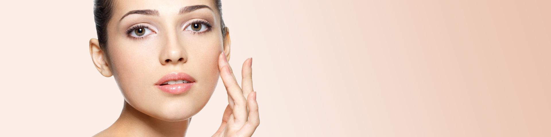 Junge Frau tippt mit 2 Fingern auf ihre Wange