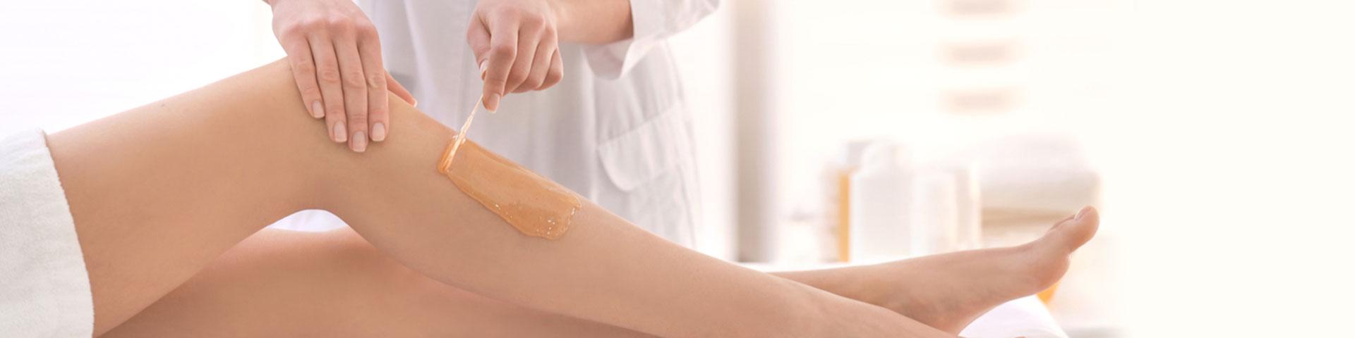 Waxing - Frauenbeine an denen geharzt wird